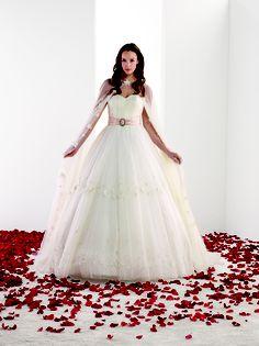 MELLE ANABELLE Robe de mariée grand volume en tulle. Buste au décolleté coeur finement drapé à la verticale.La jupe à longue traine est parsemée de petites fleurs. Ceinture amovible en satin rose à plis couchés, agrémenté d'une boucle ornée de strass à nouer dans le dos. Longue cape en tulle assortie à la robe parsemée de petites fleurs sur les bords. La robe est fournie avec une seconde ceinture de couleur ivoire. Existe en ivoire et en blanc.