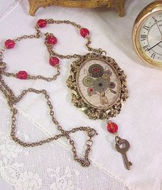 """This is an absolutely beautiful watchpart floral bouquet necklace. I mounted the watchpart """"flowers"""" in resin. The background is vintage paper. The antique gold toned vintage pendant mounting has a be"""