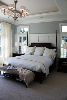 Chrome light fixture with small drum shades, blue grey walls, coved ceiling, bed, white sheers, plantation shutters and the wainscot paneling behind the bed to break up the solid blue. Light and airy.