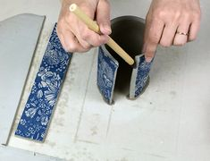 """Once you have applied an underglaze transfer onto a clay slab you can build with it. Here we will demostrate forming a handled cup with a printed slab. One underglaze transfer has a printed area that measures approximately 6"""" x 10"""", so we have a large enough area to work with. Begin by cutting out two rectangular parts, one for the walls of the cup and a smaller rectangle for the handle of the cup. The raw part of the slab can be used for the base of the cup. Use a knife to cut ..."""