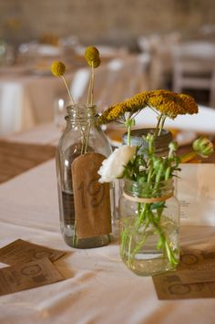 Glass milk bottle decorated with kraft paper for the table number + mason jar vase.  LOVE!