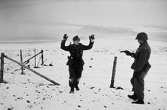 Robert Capa © International Center of Photography BELGIUM. Near Bastogne. December 23rd-26th, 1944. A US soldier with a German prisoner of war during the Battle of the Bulge.