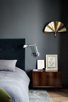 dd this is a great scheme of colours and textures and reflections. We have the dark grey/blue of the headboard which is velvet and absorbs, the mid-grey tone of the walls, the redish tone of the wood and the gold accent. Also look at the grey in the bed and on the floor and a small amount of green/yellow