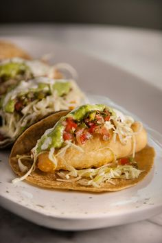 Tacos de pescado en Agua y Sal Cebicheria. Deep fried beer-batter white fish, cabbage relish, fresh Pico de Gallo salsa, (tomato, onion, Jalapeño pepper, cilantro and a touch of lime juice) avocado salsa verde and a creamy mayonnaise dressing served on corn tortilla