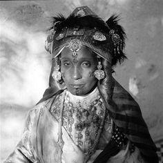 - Besancenot Jean (1902-1992) - Portrait d'une citadine de Meknès en costume de fête. Les boucles d'oreilles et le collier lebba sont des modèles anciens. Le diadème, taj, est recomposé avec des éléments anciens. De chaque côté du visage les boudins, demouj, les cornes, sont enveloppés par la soierie de lamé rouge et or et contribuent à écarter fortement sur la largeur le volume de la coiffure. Sur le visage sont collés de petits décors de papier noir.- Arago