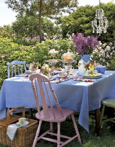 Throw a garden tea party with pastel colors, unique colored chairs, and flowers to decorate the tabletop.