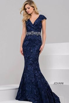 Featuring a mermaid silhouette in embroidered lace, this Jovani 37588 evening dress charms with a pleated V-neckline that folds into the cap sleeves. The surplice bodice tapers to the crystal beaded waist, capping the curve-hugging skirt that flares to a court train. Available in sizes 00 to 24.