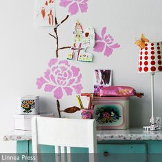 Romantische Wandbemalung für´s Home Office: Mit abstrakten, rosafarbenen Blüten an der Wand und liebevollen Kinderzeichnungen avanciert der Arbeitsplatz zum  …
