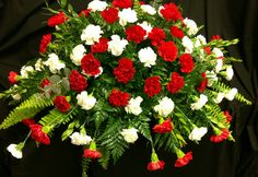 Red and white carnations casket spray created by Pam Roberts.