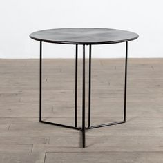 With clean lines and a simple construction, this round black accent table is sure to add a contemporary touch that will complement any home decor. Crafted of iron, this coffee table was handmade by artisans in India.