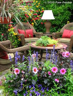 Cottage garden patio with wicker furniture and an abundance of flowers.