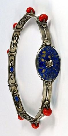 Sah Oved - A rare Arts and Crafts silver, lapis lazuli and coral belt, British, circa 1940. The front designed as an oval lapis lazuli buckle with engraved foliate detail, the waistband decorated at intervals with large coral beads between geometric sections of architectural form.