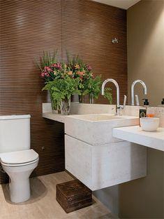 No lavabo, uma parede de nogueira com ripas de 1 cm para garantir leveza. Nas demais paredes, o tom fendi contrasta com o piso e a cuba de mármore travertino romano, mesmo material da bancada, que tem espaço para acomodar vasos, bowl e sabonete líquido. Repare que a cuba profunda esconde o sifão.