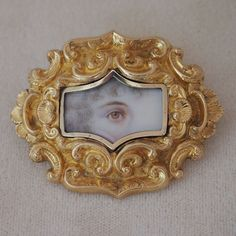 A very rare hand-painted lover's eye brooch depicting a woman's eye with curling tendrils of hair on the left side. This miniature portrait is framed by yellow gold worked in repousse style, and finished with a narrow inner fluted frame. The brooch is English, circa 1820-1840.