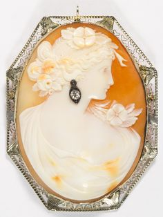 Lot 609: 14k White Gold Framed and Diamond Carved Shell Cameo Pin / Pendant; Lady wearing an earring having a 0.10CT diamond, support and pin bar, swing up pendant loop