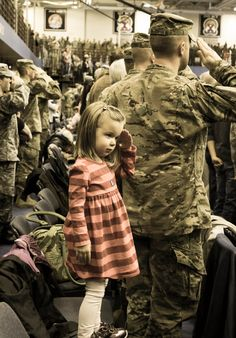 Daniella Moen, 3, daughter of Chaplain (Captain) Dan and Sasha Moen, salutes during the national anthem at 1st and 2nd Brigade Combat Team's combined deployment ceremony at MaGrath Sports Complex Jan. 11 on Fort Drum, NY.