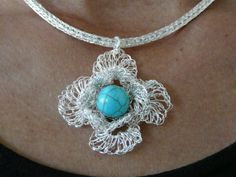 necklace is tightly knitted with silver plated and non tarnish wire. The flower is crocheted with a turquoise bead in the middle. Unique item!