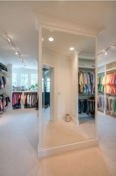 Giant wall mirror dividing the his and hers spaces in this closet.