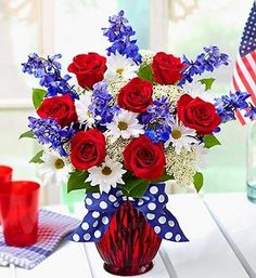 With Distinction. Red, white and blue flowers. Patriotic cowansrosepetalflorist.com