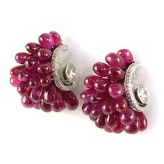 Pair of ruby drop cluster and diamond earrings by Viren Bhagat, Mumbai, designed as tapered half-hoops set face-out with polished ruby drops, a diamond set scroll to each side terminating in a collet set round brilliant cut diamond