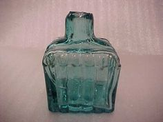 Burst top, square, ribbed, 2 pen rest with  aqua glass British ink bottle of the mid 19th Century. There were burst tops, sheared tops, cracked off tops, all are methods used to remove the hot and just blown bottle from the blowpipe.