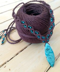 This is a handmade chocolate-brown macrame hemp necklace with sliding bead closure featuring turquoise colored magnesite pendant and teal glass beads.