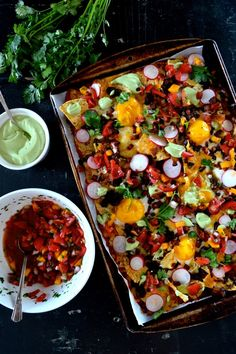 layer on the bottom of a baking sheet or baking dish. Add a layer of chips over the salsa, then a layer of beans/cheese, another layer of ch...