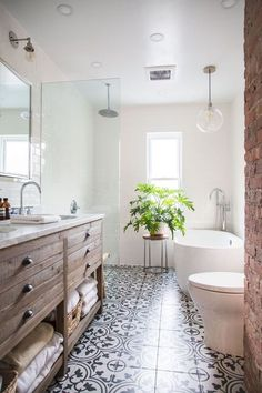 The patterned tiled flooring, wooden sideboard and modern bathtub styled with pendant lighting and an eye catching plant look so inviting in this bathroom!