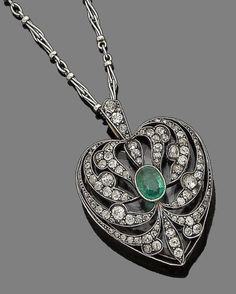 An emerald and diamond heart pendant necklace, circa 1890.  Millegrain-set to the centre with an oval-cut emerald, within an openwork surround of cushion-shaped and rose-cut diamonds, glazed compartment to the reverse, mounted in silver and gold, suspended from a later fancy-link chain, diamonds approx. 1.80cts total, French assay mark, lengths: pendant 4.0cm, chain 51.0cm