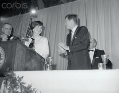 """jacqueline-the-american-queen:    President Kennedy applauds his wife Jacqueline as she is introduced at a nationwide closed circuit tv show, """"An American Pageant of Arts"""", at the Washington, DC National Guard Armory  December 29, 1962"""