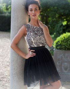 Short dress with high neckline, black skirt, white sheer top, sweetheart panel underneath, and black and white detail on bodice