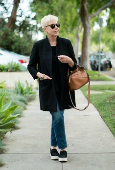 A minimalist look with a black jacket and structured bag. Details at une femme d'un certain age.
