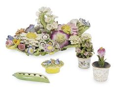 AN ENGLISH PORCELAIN FLOWER-ENCRUSTED TABLE ORNAMENT, <br />19TH CENTURY, <br /><i>together with</i> thirteen porcelain miniature potted plants, various makers; a basket with two doves; and a pea pod<br />The table ornament 9¾in. (24.7cm.) long (16)<br />