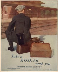 """Vintage kodak camera travel ad poster. Features a young man sitting on his luggage at a train station platform with a camera case slung over his shoulder.  """"Take a Kodak with you"""". 1915"""