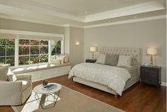 Serene...Lovely Bedroom Design with Tan Window Seat, Large Windows, Tan Chair, and White and Gray Bedding. Find more on Home and Garden Design Ideas.