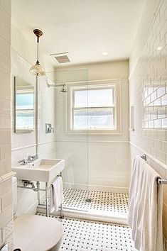 Clean and simple white bathroom with subway tiles and basket weave floor tiles