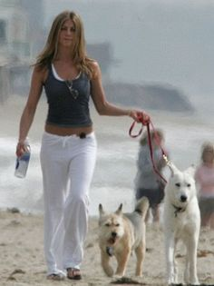 Jennifer Anniston walking the dogs on the beach.