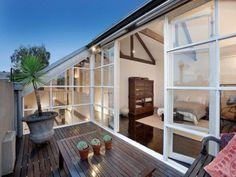 格子入りのガラスで囲われた中庭的な作りのバルコニーの屋外リビング ベッドルームに隣接