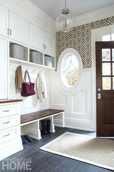 Well appointed white and brown mud room features upper walls clad in David Hicks La Fiorentina wallpaper and wainscoted lower walls lit by a Regina Andrew Large Globe Pendant hung from a gray ceiling over a diamond patterned jute rug placed on slate tiles.