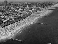 Aerial view of crowds enjoying miles of boardwalk & beach at Coney Island on a hot 4th of July, Brooklyn, NY, July 4, 1946
