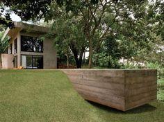 Concreto, vidro e linhas retas caracterizam este projeto, do arquiteto goiano Leo Romano. Nos seus 290 m² quase não há paredes. As que sustentam a edificação deixam o concreto aparente, inclusive do lado de dentro. Aproveitando a robustez do material, a ponta da raia da piscina paira no declive do terreno. Mais uma vez, o concreto permite flutuar.