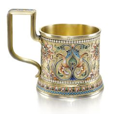 A silver-gilt and cloisonné enamel tea glass holder, maker's mark V.A. (Cyrillic), Moscow, 1899-1908, enamelled in shaded polychrome foliage on a stippled ground within white dot borders, the squared handle with turquoise ground.