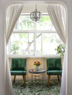 Pretty white archway, simple cotton/linen drapes. Shiny retro green chairs in seating alcove. Galvanised metal table, graphic green and white rug and cool glass pendant.