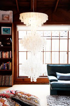 A living room featuring a large chandelier made of shells.