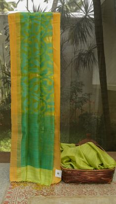 This bright sari is a beautiful blend of matka silk and kora in lime green. The border is marked by a bands of merigold orange and gold zari. This sari has a rich pallu with sea green floral motifs…