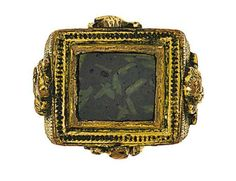 A 16th century gilt 'Papal' ring   The large ring set with an opaque dark green Roman paste rectangular panel, the heavy gilt mount engraved and decorated on the sides with the symbols of the evangelists in high relief, the hoop engraved with an armorial shield flanked by the inscription PIUS PAIX, circa 1580