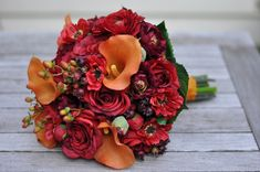 Vibrant fall wedding bouquet made of silk flowers, orange calla lily, red roses, ranunculus, berries.