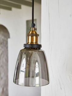 Installing refined lighting is an instant way to usher a timeless atmosphere into your home, and these elegant smoked glass and brass pendants do so to perfection.
