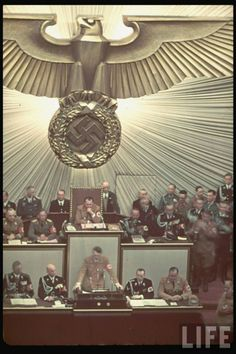 A colored look inside the Reichstag. Seen here, Adolf Hitler addresses the German government,  while a gorgeous and imposing golden imperial eagle dominates the background.