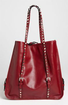 Valentino 'Rockstud' Leather Shopper    A gilded logo highlights one side of a creamy leather shopper enhanced with shining studs for a fashion-forward finish.    Magnetic-snap closure with adjustable bridge strap.    Interior zip, wall and cell phone pockets.    Vitello leather.    Made in Italy.
